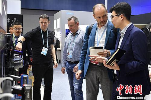 """4月15日,一家电品牌参展商为采购商介绍产品性能。在第123届中国进出口商品交易会(广交会)上,来自34个国家和地区的617家企业在进口展区内展示产品,其中来自21个""""一带一路""""沿线国家和地区的382家企业参展,展位数626个。<a target='_blank' href='http://www.chinanews.com/'>中新社</a>记者 陈骥�F 摄"""